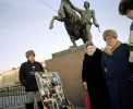THREE PEOPLE AND POSTER IN FRONT OF EQUESTRIAN STATUE, ST PETERSBURG