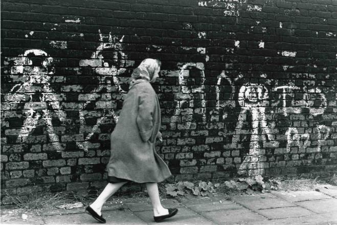 Lady walking past graffiti strewn wall