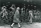 Lady walking past graffiti-strewn wall - Salford 1964